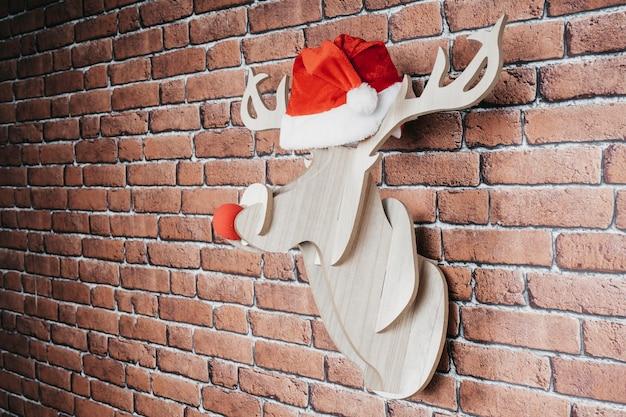 Intarsienhirsch hängen an der wand mit weihnachtsmannhut und roter nase. weihnachtsdekoration