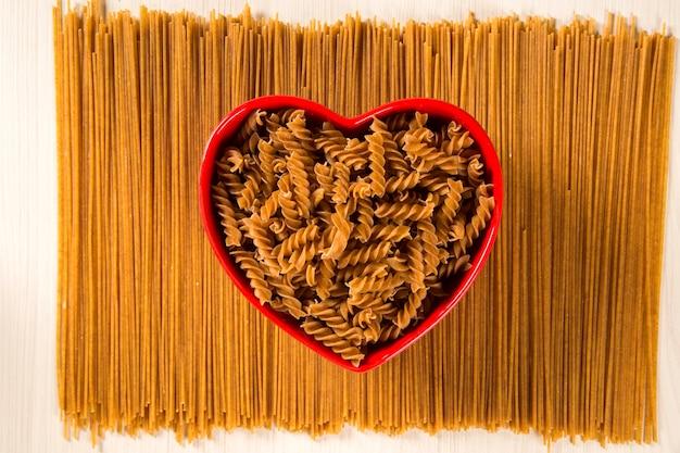 Integrieren sie fusilli in eine herzschale über spaghetti