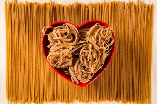 Integrierte tagliatelle in eine herzschale über spaghetti