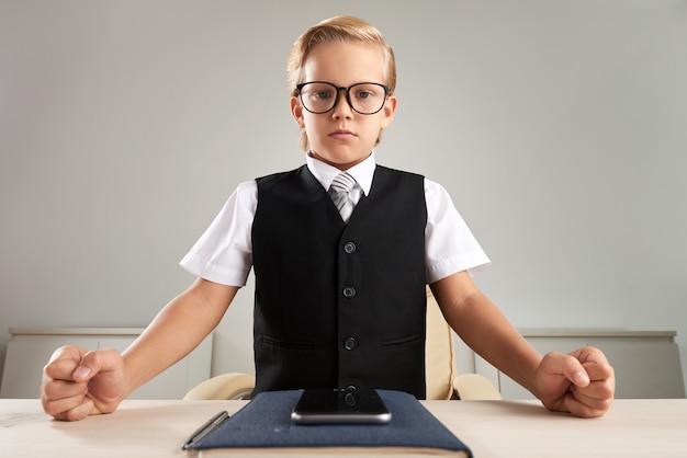 Intelligent gekleideter kaukasischer junge, der im büro steht und fäuste auf schreibtisch zuschlägt