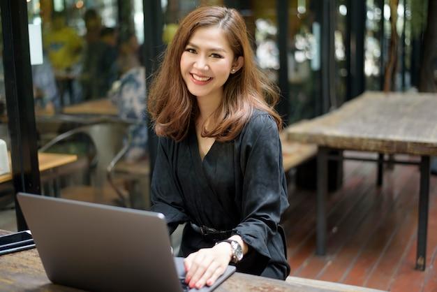 Intelligente asiatische frau arbeitet mit laptop-computer