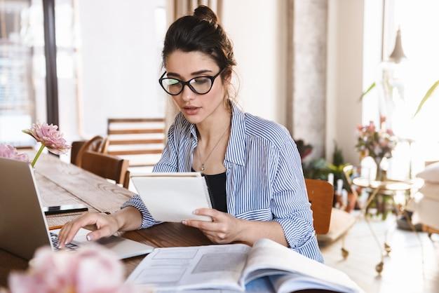 Intelligente brünette frau in der freizeitkleidung, die auf laptop schreibt, während sie zu hause arbeitet oder studiert