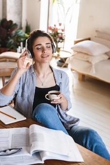 Intelligente entspannte frau in kopfhörern, die musik hören, während sie mit heften zu hause lernen