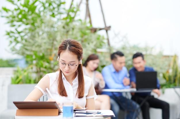 Intelligente ernsthafte vietnamesische studentin, die musik in ohrhörern hört, wenn sie am kaffeetisch im freien sitzt und am projekt arbeitet