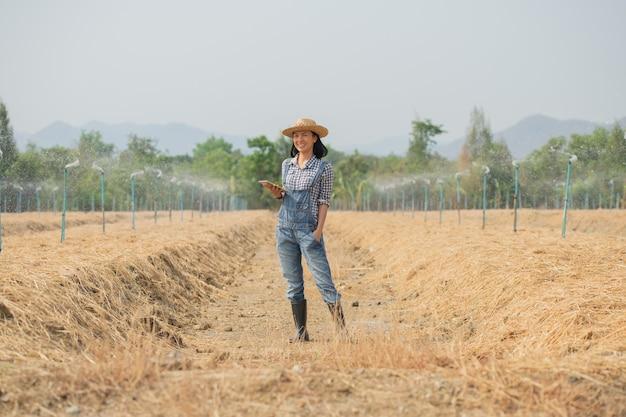 Intelligente farm. schöne landwirt verwenden tablette, um ihre farm und geschäft mit glücklich und lächeln zu steuern. geschäfts- und landwirtschaftskonzept. landwirt oder agronom untersuchen, bereiten ein grundstück für den anbau von gemüse vor.