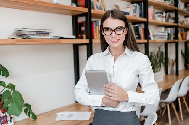Intelligente frau im büro mit dem tablettenlächeln