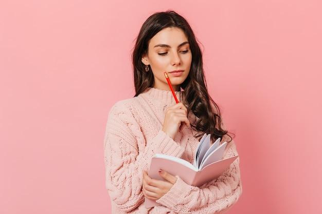Intelligente frau im rosa pullover denkt über die fortsetzung ihres buches nach. brünette schaut in ihrem tagebuch auf rosa hintergrund.