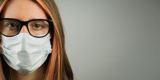 Intelligente frau in brillen, die medizinische maske tragen, kopieren raumbanner.