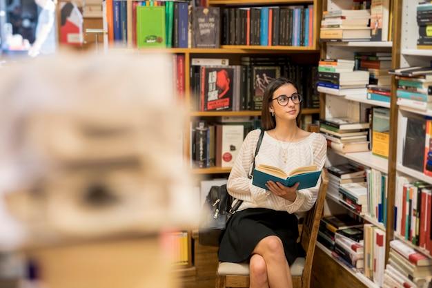 Intelligente frau in den gläsern, die mit buch in der bibliothek sitzen