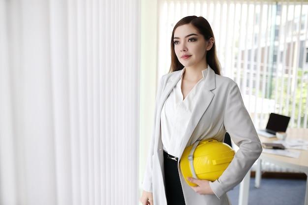 Intelligente geschäftsfrau mit dem klagenhandgriff-ingenieursturzhelm, der im geschäftslokal steht