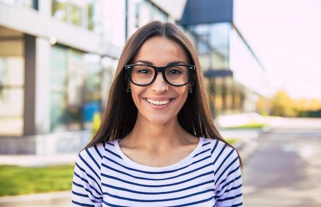 Intelligente geschäftsfrau mit lässigem outfit und brille posiert mit verschränkten armen, schaut nach links und lächelt aufrichtig