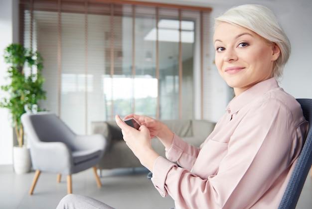 Intelligente geschäftsfrau mit smartphone, die kamera anschaut