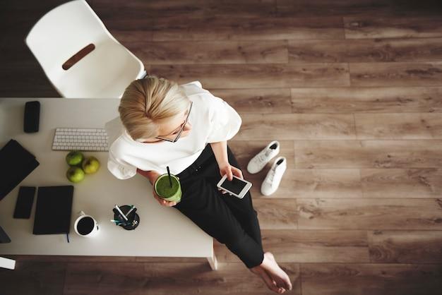 Intelligente geschäftsfrau mit smoothie und smartphone am schreibtisch sitzend