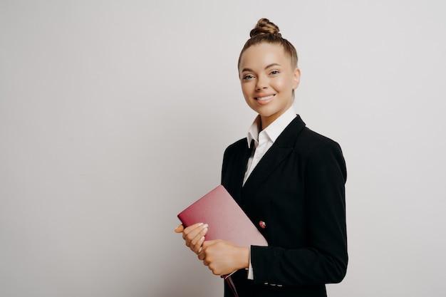 Intelligente, glückliche geschäftsfrau oder büroangestellte, informelle kleidung, die ein rotes notizbuch mit wichtigen informationen hält und gerne in die kamera lächelt, isoliert auf hellem hintergrund posiert