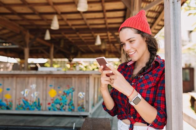 Intelligente hipster-frau mit dem schönen lächeln, das auf smartphone mit entzückendem lächeln im sonnenlicht rollt. frau mit weißen zähnen und gesunder haut mit smartphone außerhalb