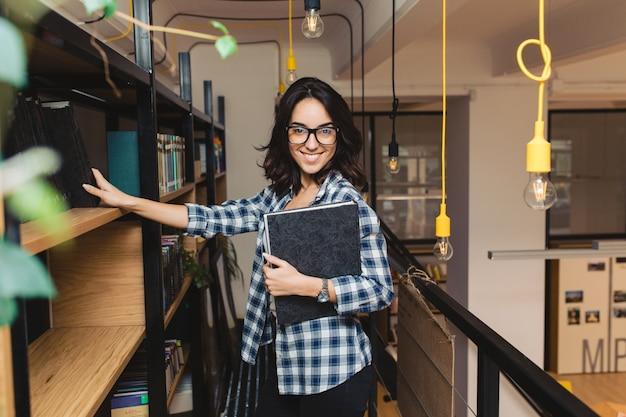 Intelligente hübsche junge brünette frau in den schwarzen gläsern, die mit buch in der modernen bibliothek lächeln. universitätsleben, kluger student, fröhliche stimmung, ausdruck wahrer positiver emotionen.