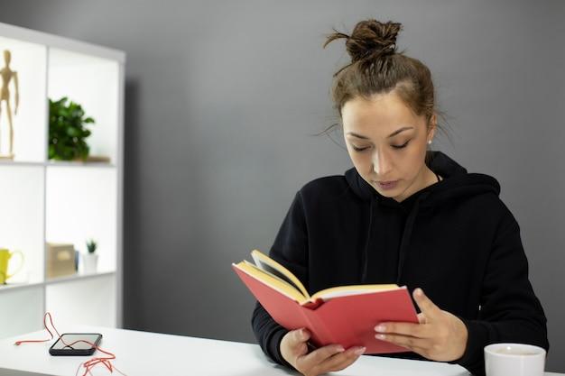 Intelligente junge frau im schwarzen hoodie-lesebuch. selbstbildung während covid-19