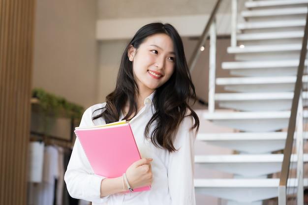 Intelligente junge geschäftsfrau, die weißes hemd und blaue jeans hält, die rosa buch hält, das vor der treppe im konzept des geschäfts erfolgreich steht