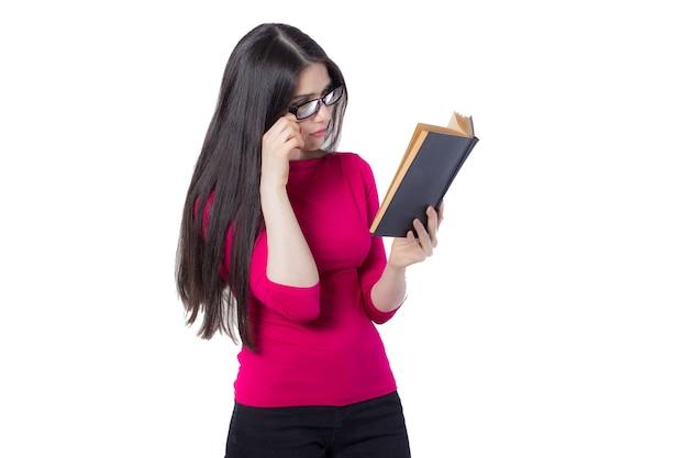 Intelligente junge studentenfrau in rotem hemd und brille, die schwarzes buch in einer hand hält, auf weißem hintergrund, interessierte konzeptidee der frau liest