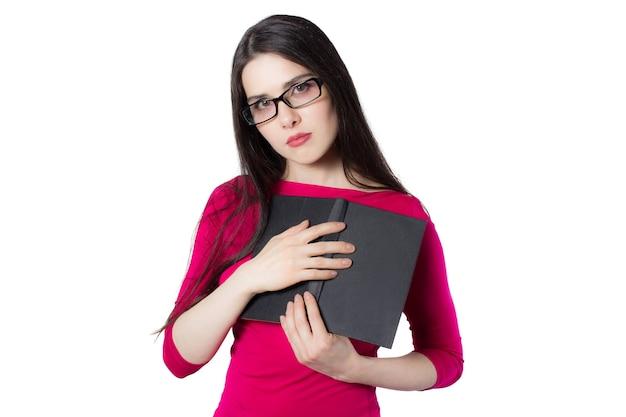 Intelligente junge studentin in rotem hemd und brille, die ein schwarzes buch an ihr herz drückt, auf weißem hintergrund, konzeptidee für die wissensfrau