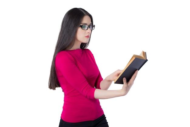Intelligente junge studentin in rotem hemd und brille, die ein schwarzes buch in einer hand hält, auf weißem hintergrund, konzeptidee der wissensfrau liest