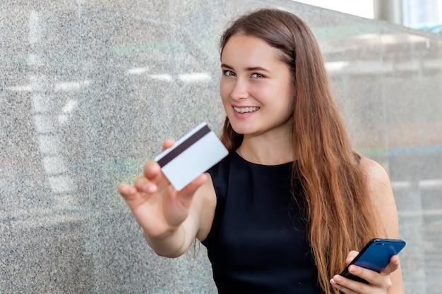 Intelligente kaukasische frau, die online mit einer kreditkarte und einer smartphone-anwendung kauft.
