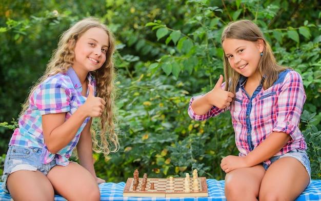 Intelligente kinder kinder spielen schach im freien naturhintergrund sport- und hobbykonzept