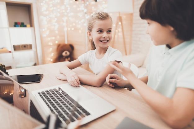 Intelligente kinder machen hausaufgaben mit laptop boy hilft mädchen.