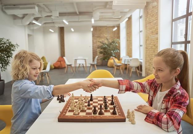Intelligente kleine kinder, junge und mädchen, die sich nach dem spiel die hände schütteln, um brettspiele zu spielen, die zusammen sitzen?