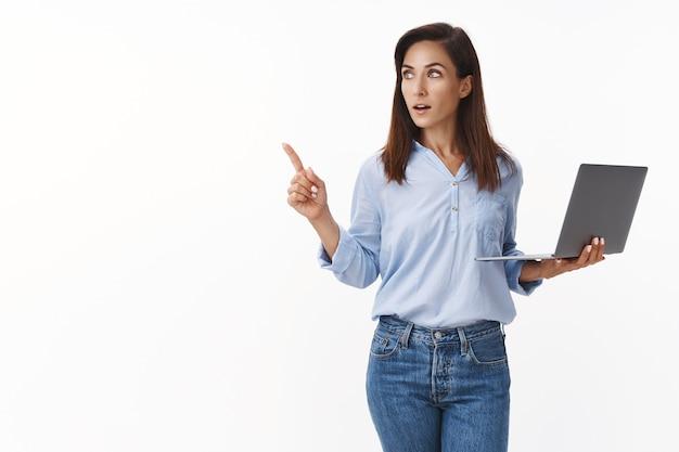 Intelligente, kreative, beschäftigte unternehmerin, die anweisungen gibt, mitarbeiter verwalten das geschäft, halten laptop, arbeiten, zeigen kopien beiseite, heureka-geste, biegen sie links ab, haben sie eine idee, stehen sie weiße wand