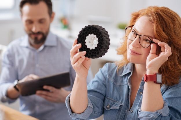 Intelligente kreative schöne frau, die ein 3d-modell hält und ihre brille repariert, während sie es betrachtet