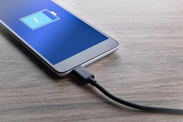 Intelligente mobiltelefone, die auf weißem hintergrund des hölzernen schreibtisches aufladen