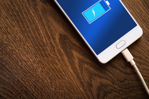 Intelligente mobiltelefone, telefon, das auf hölzernem schreibtisch auflädt