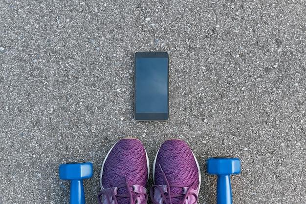 Intelligente sportgeräte. abgeschnittenes foto von dumpbells und lila turnschuhen auf asphalthintergrund. mobile apps zur sportmotivation