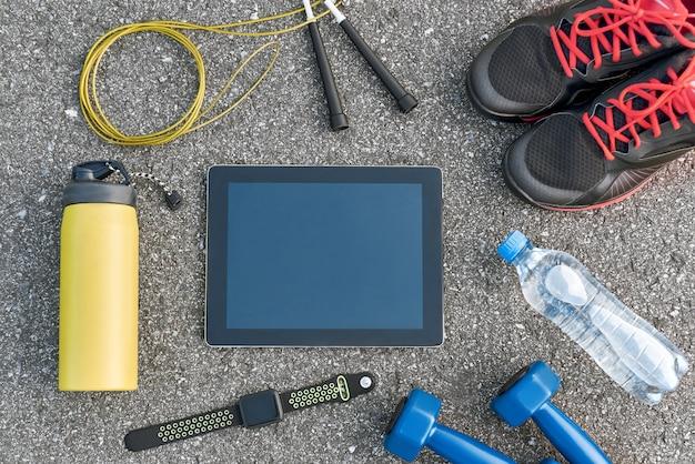 Intelligente sportgeräte. abgeschnittenes foto von dumpbells, wasser, springseil und schwarzen turnschuhen auf asphalthintergrund. mobile apps zur sportmotivation