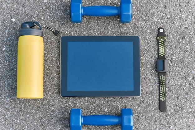 Intelligente sportgeräte. abgeschnittenes foto von dumpbells, wasser und smartwatch auf asphalthintergrund. mobile apps zur sportmotivation
