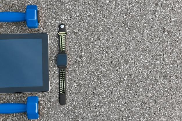 Intelligente sportgeräte. abgeschnittenes foto von smartwatch, wasser und schwarzen turnschuhen auf asphalthintergrund. mobile apps zur sportmotivation