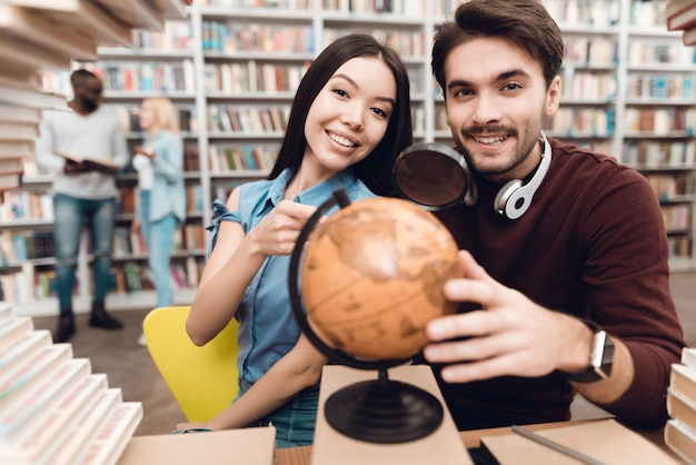 Intelligente studenten verwenden globe in der bibliothek