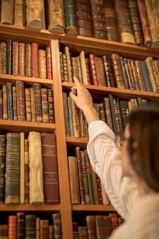 Intelligente studentin, die nach buch in der bibliothek sucht