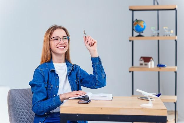 Intelligente studentinnen bekommen eine unerwartet gute idee, wenn sie zu hause studieren. die studentin kommt zu materiellem verständnis oder erreicht den punkt, an dem sie im coworking office studiert.
