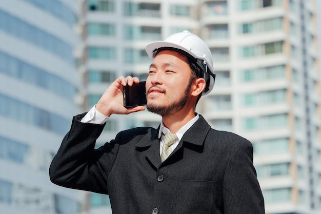 Intelligente technik, die am telefon spricht und an im freien, glückliches teamwork-konzept arbeitet.