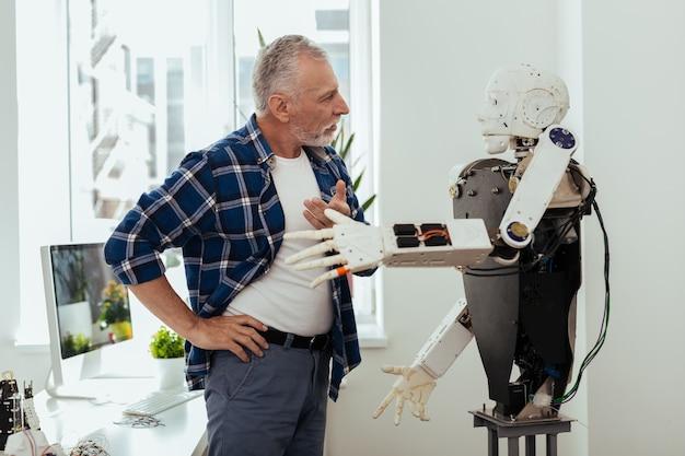 Intelligente technologie. ernsthafter alter mann, der den roboter betrachtet, während er ein gespräch mit ihm führt