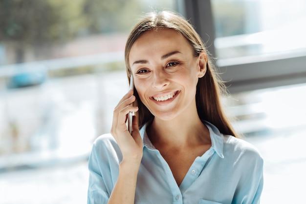 Intelligente technologien. fröhliche attraktive junge geschäftsfrau, die am telefon lächelt und spricht