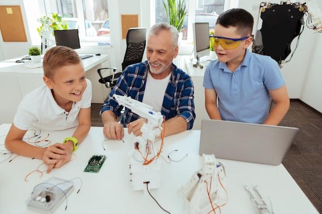 Intelligente technologien. glückliche aufgeregte schüler, die am tisch stehen, während sie den roboter betrachten