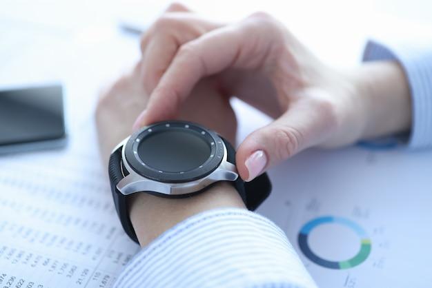 Intelligente uhr mit schwarzem armband an der hand der frau, die moderne geräte verwendet, um das geschäft zu steuern