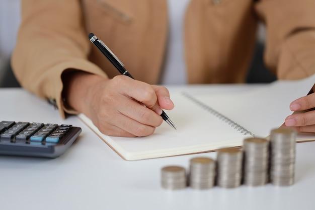 Intelligente und aktive asiatische geschäftsfrau, die hände schreibt, die etwas auf dem notebook schreiben, indem sie beim stapeln von münzen auf dem tisch wachstum sparen, was bedeutet, geld oder investitionen oder steuern für das geschäftswerbekonzept zu verdienen