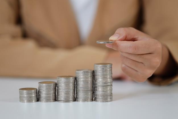 Intelligente und aktive asiatische geschäftsfrauhände, die auf dem stapeln von münzen festhalten, die auf weißem tisch und weißem hintergrund wachsen, was bedeutet, geld oder investitionen oder steuern für das geschäftswerbekonzept zu verdienen