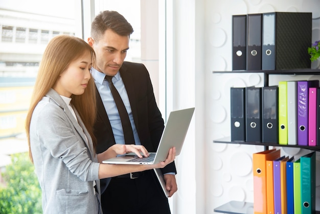 Intelligenter chef und sekretär, die zusammen mit laptop im büro arbeiten.