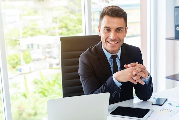 Intelligenter geschäftsmann, der mit laptop auf schreibtisch im büro arbeitet.