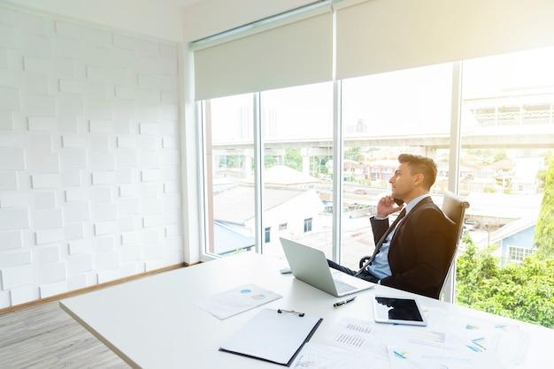 Intelligenter geschäftsmann unter verwendung des mobiles, zum mit leuten im büro in verbindung zu treten